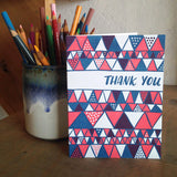"white greeting card with a red and blue illustrated triangles pattern and hand lettering that reads ""thank you"" photographed next to a cup of pencils"
