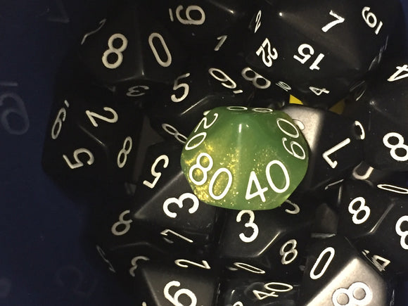 A brilliant green percentile dice among a pile of black dice