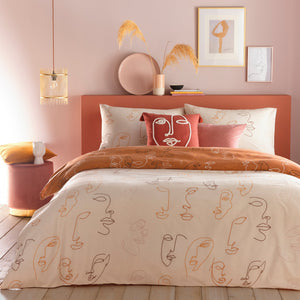 Hand drawn faces on peach duvet cover woth rust ornage coordinating reverse. Bed set against a light pink bedroom wall.