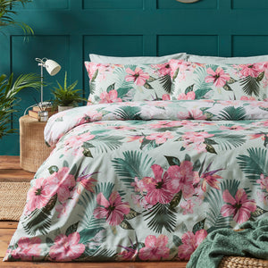 Duvet set on a bed featuring pink tropical flowers and green leaves on a light blue green base. Bed is set against a green bedroom wall.