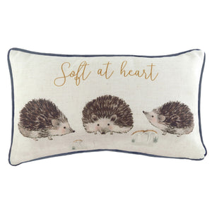"off-white rectangular cushion with blue piping featuring 3 painted hedgehogs and a quote reading ""soft at heart"""