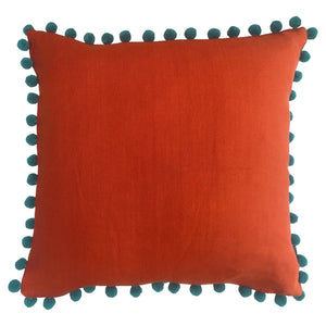 orange square cushion with teal blue pom pom trim