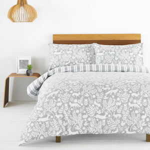 grey duvet set with white pattern of forest animals and leaves and a grey on white stripe reverse
