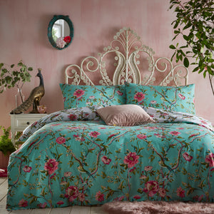Turquoise blue green duvet set featuring swirling floral vines and beautiful exotic birds, with a coordinating design on the reverse, on a fresh, light blue base. Set against a pink bedroom wall.