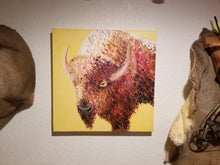 A big brown buffalo stares, bemused, against a backdrop of an autumn yellow. This square painting is hung on the wall of your favorite taxidermist's office, between two pelts.