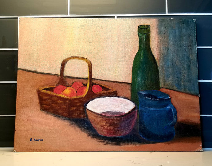 A classically styled oil painting portrays a perfect pile of a basket, apples, a mug, and a bottle of wine. This First Edition Original Painting is called