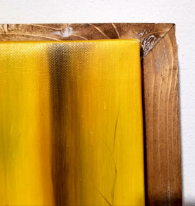 "The corner of the painting ""A Flower For The Fire"" owned by FirstEditionAcquisition.vision. The corner of the canvas is orange variety and the wood is a light wood, that has been stained with a wood stain I deem as ""Extra""."