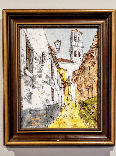 Seen here is a speculated antique painting of a street lined by concrete buildings appearing to be of Spanish influenced architecture. At the end of the yellow street is a large eg shell collared building casting a bell tower or steeple at the blue sky backdrop. It is an original oil painting acquired and owned by FirstEditionAcquisition.Vision