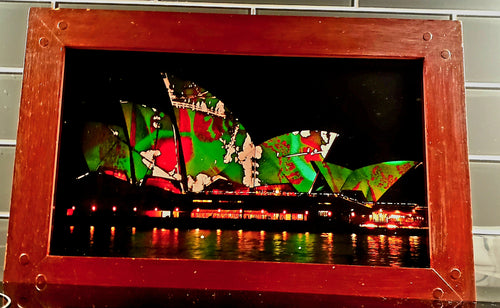 This photo of a picture is presented with the filter found on the photographer's phone. A gray tile backdrop breaks the monotony of previous product pictures. The Sydney Opera House is the subject of this shot and it is shon sitting next to a shimmering bay and colored a startling red and green is stark contrast to the usual eggshell white.