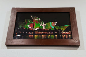 A perfect picture of Austrailia's Sydney Opera House with a green and red projected pigment on the familiar face of the fans famous amungst frequent fliers and opera enthusiasts alike. It is encompased within a finished wood frame and protected by a pane of gorgeous glass.