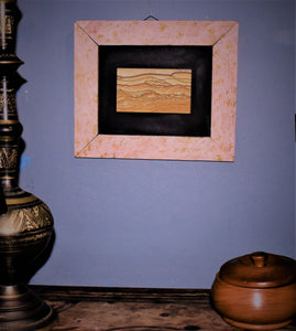 """A Glint of Gold"" is seen hanging between a bowl and a bowl on a wall."