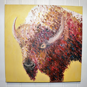 Believe it or not, a better photograph of a square painting of the bust of a buffalo facing to the left side of a square painting and perfectly painted against a yellow backdrop. This piece of perfection hangs on a very expensive white wood wall.