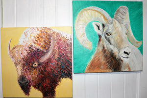 Two paintings, both alike in subject content. A buffalo on yellow and a ram lay on green. Where wary ram stare brings on new scrutiny. Ancient artisinal abilities make a clear superior of the two unclear.
