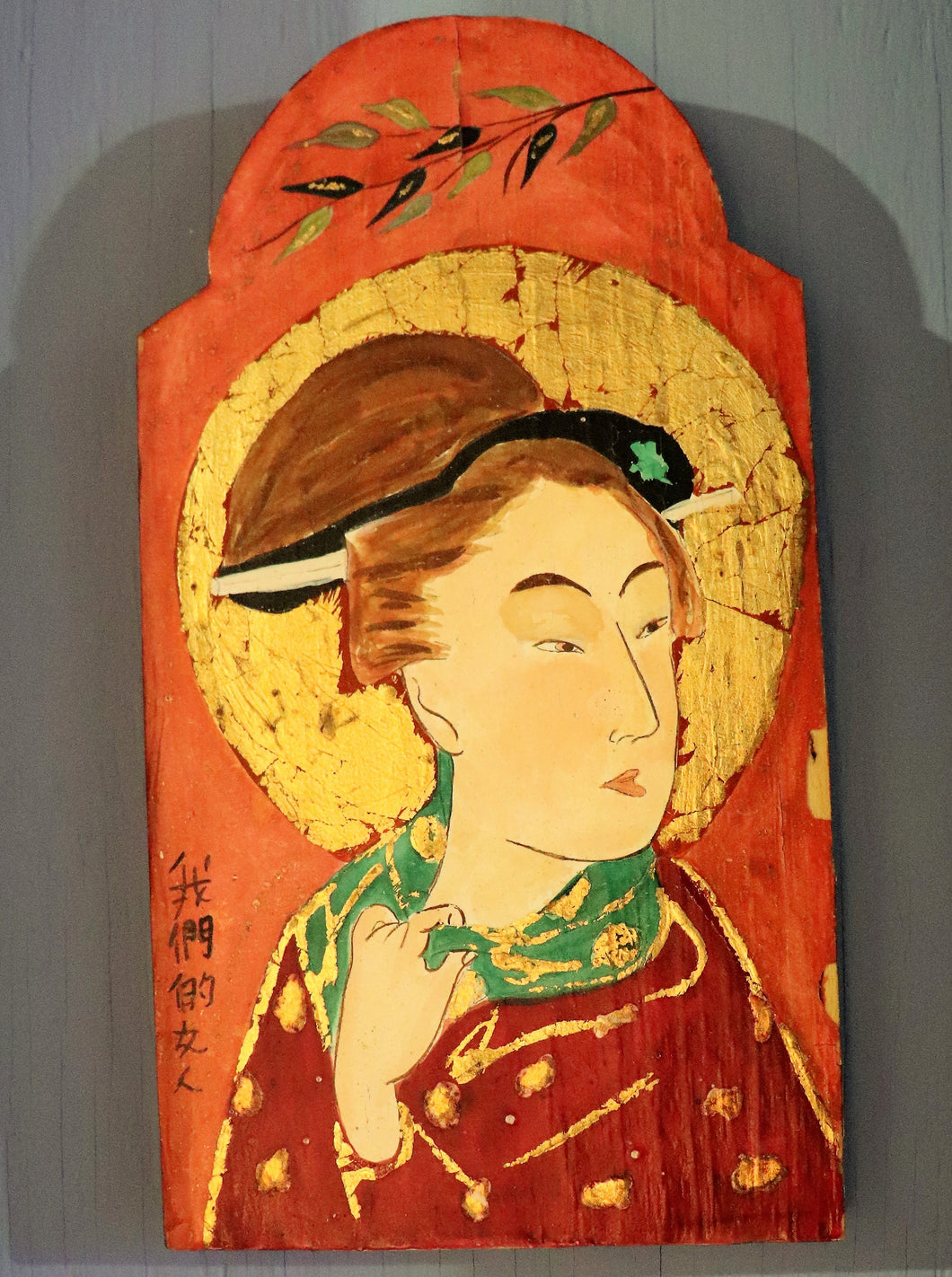 A vertically rectangular wooden plank with a rounded top has a gorgeous geisha glancing over her shoulder to the right. Her head is surrounded by a background of gold while the majority of the background is a warm orange tone.