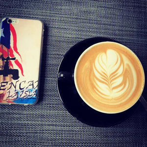 Café of Cellphone Safety! A Power To Puerto Rico iPhone case casually coincides to left of a cup of crafted caffinated coffee and cream.