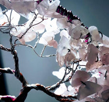 zoomed in view of the rose quartz leaves that are white with shades of pink surrounded by twisted metal branches.