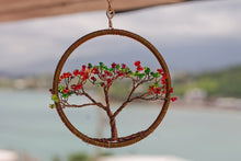 Imagine an out of focus picture of calming nature as the background.  Atop said pattern is a linked chain connected to a masterfully spun brown in the shape of a circle with a flamboyan tree in the center spun with brown wire with red and green bead tips on each branch.  A First Edition Original created by renowned artist Bill Bourdon.