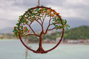 Picture a out of focus background of calm nature with an in focus circle of spun brown wire containing in the center a twisty brown wire flamboyan tree with green and yellow beads the tip of each branch.  A First Edition Original created by Bill Bourdon.