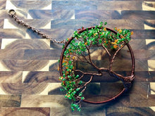 Imagine a circle of brown spun wire with a twisty tree in its center with yellow and green beads at the tip of each branch with a linked chain attached laying on top of a beautiful wood pattern background.  A First Edition Original created by artist Bill Bourdon.