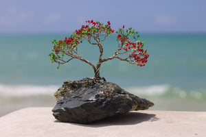 With a blue sea and a white sand backdrop, this silver wooded flambouyan tree sits atop a rock and was designed by Bill Bourdon. He has agreed to share this image with a sand setting in the foreground with First Edition Acquisition, Ltd.