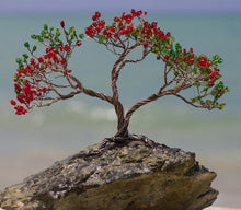 A Flambouyon made by Bill Bourdon appears in the midground and has green and red foliage in its canopy. First Edition Acquisition, Ltd. would describe the background as appearing to be a beautiful white sand beach. The tree in the middle is anchored to a rock and is made of silver branches.