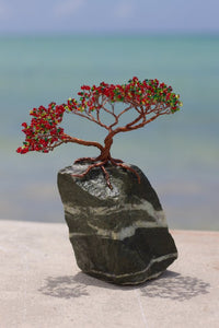 Imagine a visage containing a small rectangular rock colored grey and black with a small twisty wire spun to create the shape of a tree with many small branches all in brown with red, yellow, and green blooming beads at the ends of each.  A First Edition Original created by Bill Bourdon.