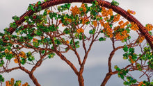 Picture a out of focus background of calm nature with an in focus, zoomed in view of a circle of spun brown wire containing in the center a twisty brown wire flamboyan tree with green and yellow beads the tip of each branch.  A First Edition Original created by Bill Bourdon.