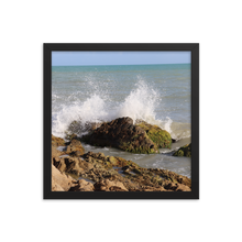 Imagine rigid rocky beach with the wet and explosive splash of an ocean wave as it playfully spreads its blue and white colors into the air.  This picture is in a square frame.  This photo was taken by trending photographer and artists Andrew Aaron in Puerto Rico.