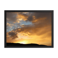 A horizontal rectangular black frame encompases a sunset of primarilly orange with blues, pinks, grays, and yellow mixed in over the silhouette of a hill.