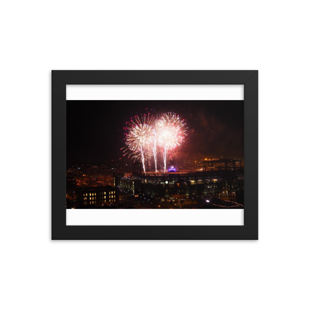 A square framed picture of a rectangular photo of fireworks exploding in the night sky above Denver's Coor's Stadium.