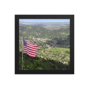 A square framed picture of an american flag atop a Puerto Rican mountain overlooking the most beautiful green valley that you ever did see.