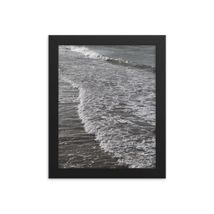 A seaside scene with wave motion from right to left is encapsulated within this vertically rectangular black frame. A gentle tide pushes a smooth sloping wave over sand so slick it appears to not make a sound.