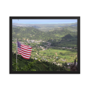 A rectangularly framed picture of an American flag atop a Puerto Rican mountain overlooking the most beautiful green valley that you ever did see.
