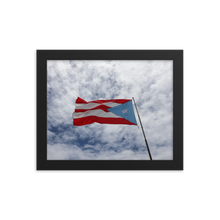 Horizontally oriented frame with image of soft, pillowy white clouds and blue sky background with a Puerto Rican flag waving to the left in the foreground