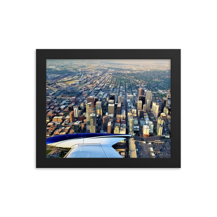 A rectangular printed photo with a black frame of a bird's eye view of downtown Denver with the sleek wing of a Cessna 310 floating in the corner of the bottom left corner of the photograph.