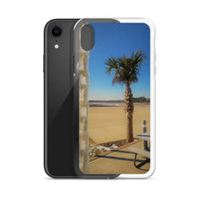 Imagine a sleek shiny iPhone case frozen to iphone with an image containing a short palm tree with a brown trunk and green spiky leaves growing from a tan and blue sandy beach against an ocean backdrop with the foreground having an ice-covered chain.  A First Edition product with picture by Victor Allen.