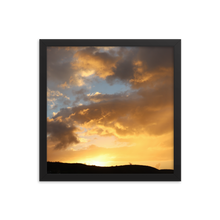 A square black frame encompases a sunset of primarilly orange with blues, pinks, grays, and yellow mixed in over the silhouette of a hill.