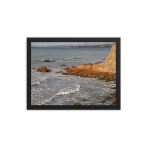 From the right side of this horizontally rectangular photo in a black frame, you see a rock jut out into the agitated blue waves of a tropical beach.