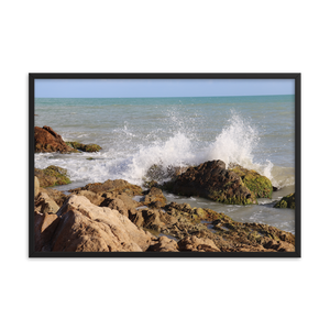 Imagine rigid rocky beach with the wet and explosive splash of an ocean wave as it playfully spreads its blue and white colors into the air.  This picture is in a rectangular frame.  This photo was taken by trending photographer and artist Andrew Aaron in Puerto Rico.