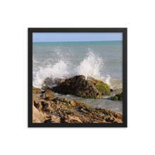 Imagine rigid rocky beach with the wet and explosive splash of an ocean wave as it playfully spreads its blue and white colors into the air.  This picture is in a square frame.  This photo was taken by trending photographer and artist Andrew Aaron in Puerto Rico.