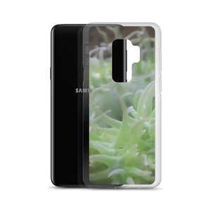 Imagine a sleek cellphone case of hard plastic wrapped around a Samsung Android phone.  This phone case is smooth and has a photo of an anemone that's neon green tentacles dance playfully in the ocean.  Photograph taken by trending artist Andrew Aaron.