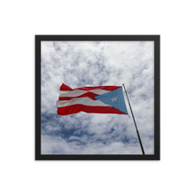 Square frame with image of soft, pillowy white clouds and blue sky background with a Puerto Rican flag waving to the left in the foreground