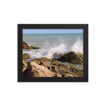 Imagine rigid rocky beach with the wet and explosive splash of an ocean wave as it playfully spreads its blue and white colors into the air.  This picture is in a rectangular frame.  This photo was taken by trending photographer and artists Andrew Aaron in Puerto Rico.