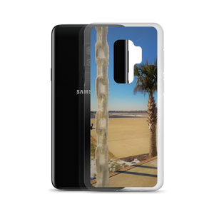 A weird winter wonderland is portrayed within this print put on a phone case. Made for one of many Samsung smartphones, you see a palm tree siting in the background of a frosted tropical area. In the foreground of this photo, an ice covered chain dangles coldly in contrast. From behind the very phone case itself, a Samsung S8+ peeks out to represent eternity in its entirety.