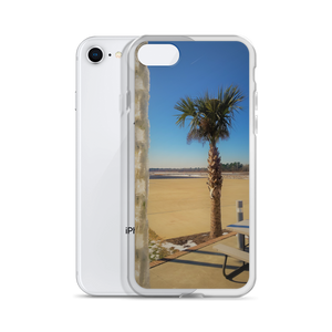 Imagine sleek shiny iPhone case snapped onto the smartphone with an image containing a short palm tree with a brown trunk and green spiky leaves growing from a tan and blue sandy beach against an ocean backdrop with the foreground having an ice-covered chain.  A First Edition product with picture by Victor Allen.