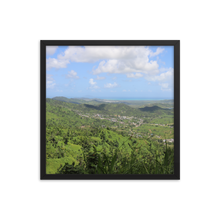 A square photo, framed in black, containing the best blue sky you ever did see littered with puffy elegant clouds floating over unbelievably lush meadows.