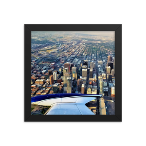 A square printed photo with a black frame of a bird's eye view of downtown Denver with the sleek wing of a Cessna 310 floating in the corner of the bottom left corner of the photograph.