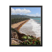 A vertically rectangular picture of paradise with a black frame displays a pristine sandy beach with gentle tropical waves rising and receding down the forest rimmed beach as far as the eye can see.