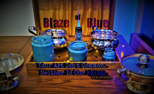 An advertisment for Blaze of Blue oil paint by FEA.Vision shows all three sizes of paint next to an open flame.
