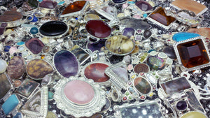 A mound of beautifully mounted gemstones in sterling silver bezels made into pendants